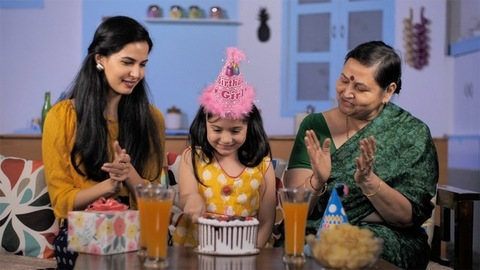 School-age girl blowing out candles on her birthday cake - party and enjoyment