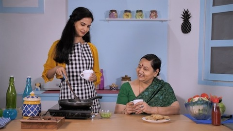 Mother-daughter enjoying evening snacks and tea while cooking in the kitchen