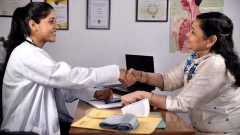 Cheerful caring physician listening calmly to a patient - senior citizen healthcare