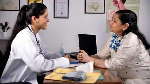 Cheerful Indian doctor talking to her patient enquiring about her health - medical concept