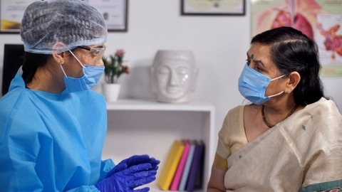 Female doctor in a protective suit talking to an elderly patient in the clinic