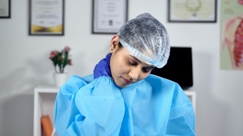 Exhausted doctor removing her surgical mask - COVID-19 epidemic spread