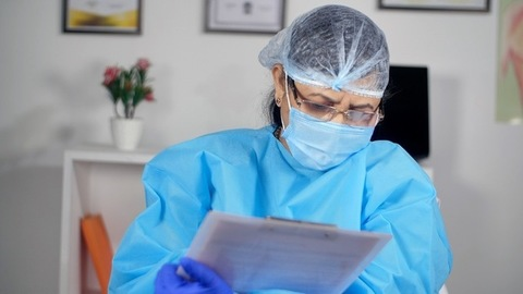 A senior doctor writing a patient's report - healthcare services during the corona epidemic