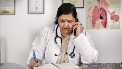Senior lady doctor prescribing medicines for a patient - remote consultation