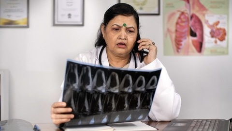Senior physician checking CT Scan / X-Ray of a patient sitting in her clinic