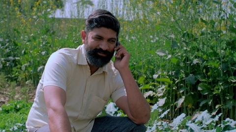 Confident Indian villager talking on mobile sitting near an agricultural area