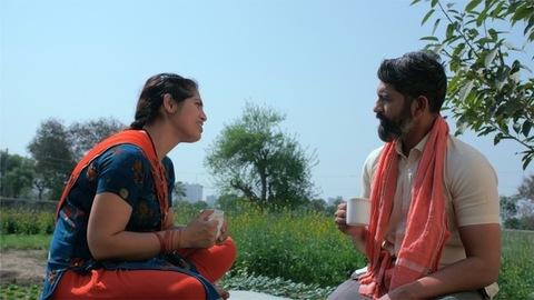 Middle-aged rural couple having a tea break during their hard work in farmland