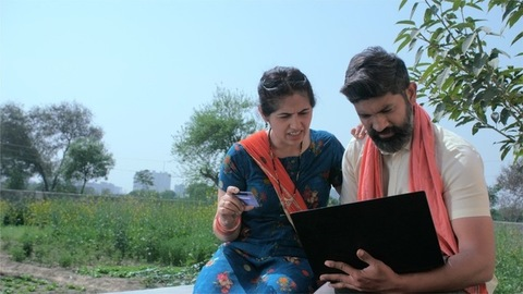 Village couple doing payment using a laptop and ATM card, online shopping - Indian farmer
