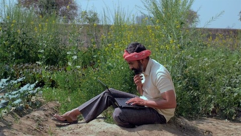 Educated Indian farmer learning new things on a laptop - modern technology