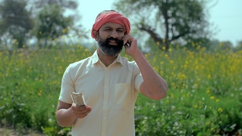 Worried Indian farmer talks on mobile about his monthly income - agricultural business