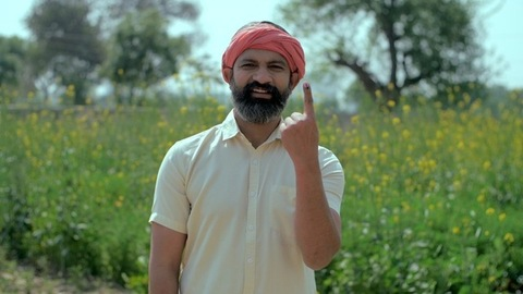 A happy Indian farmer showing his ink-marked finger and his belief in a right to vote