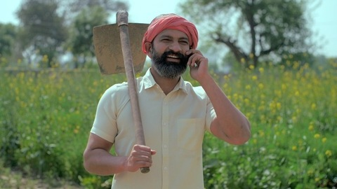 An Indian villager happily talking on his mobile while standing in his field