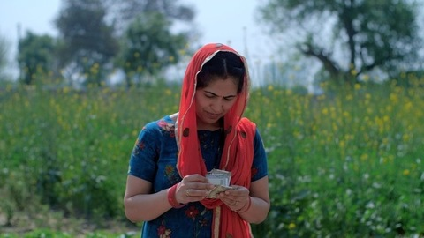 Female agricultural laborer happily counting her income standing in a field - Indian farmer