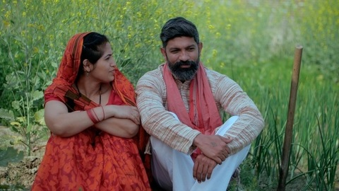 Cheerful villagers sitting in a green area talking about their agricultural work - Indian farmer family