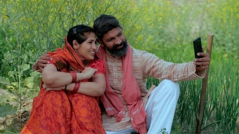 Loving village couple taking their selfie while sitting in a green agricultural area