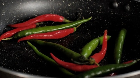Red and green chilies falling inside a non-stick frying pan - Asian cuisine