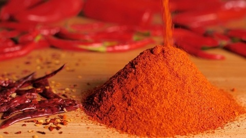 Roasted red chili powder falling on a wooden table - Indian spices