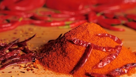Whole red chilies dropping on a heap of chili powder - tropical hot spices