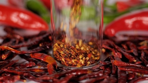 Flakes of red pepper falling inside a transparent bottle - spices and seasoning