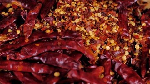 Exotic red pepper flakes and dried whole chilies dropping on a wooden table