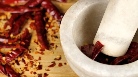 Air-dried roasted red chilies (lal mirch) falling inside a white marble mortar pestle