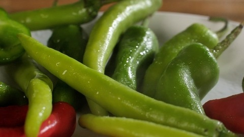 Some fresh raw green and red chilies (hari and lal mirch) with a stream of water - Indian spice