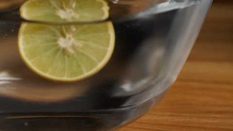 A freshly cut half lemon falling into a transparent bowl of cool pure water