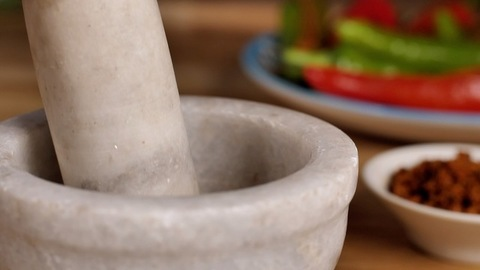 Traditional stone mortar pestle pounding ingredients to prepare spicy Masala