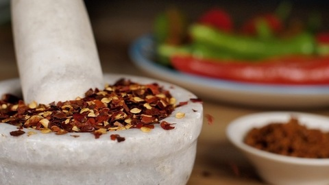 Red chili flakes dropping in a white stone mortar pestle - spicy Indian food