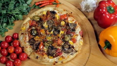 Grated cheese falling on vegetarian pizza topped with corn and olives