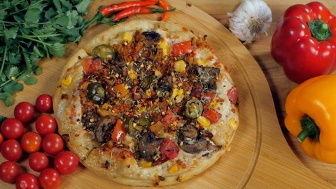 Red chili flakes falling on a freshly baked pizza with corn, cheese, and olives