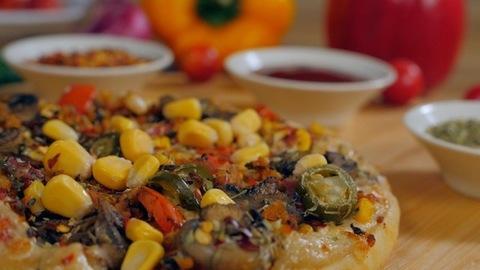 Sweet corns falling on a freshly baked homemade vegetarian pizza - tasty food