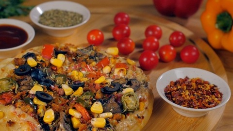 Black olives dropping on a homemade crispy pizza - Italian recipe