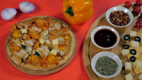 Cheese cubes falling on a freshly baked Indian Paneer pizza - healthy recipe