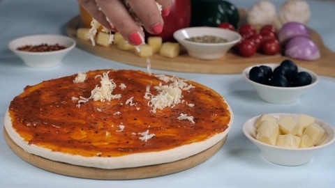 Lady chef putting grated cheese on a pesto sauce spread pizza base
