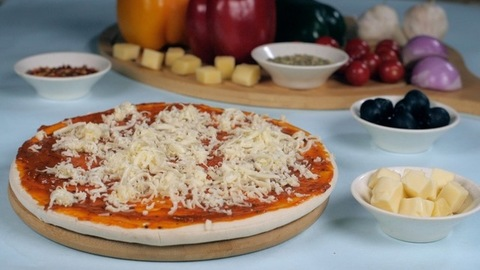 Grated cheese falling on a freshly baked pizza base - preparing Italian cuisine