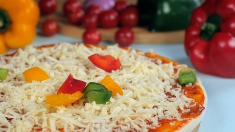 Red, yellow, green bell peppers  dropping on a pizza base loaded with cheese