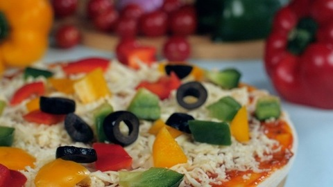 Black olives dropping on a pizza base topped with cheese and bell peppers