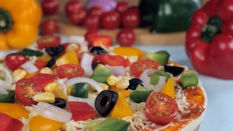 Sweet corn dropping on a delicious pizza topped with black olives and tomatoes
