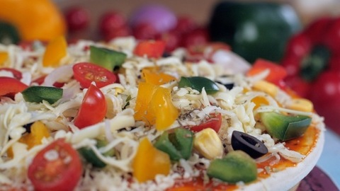 Oregano / mixed herbs on a vegetarian pizza topped with cheese and corn