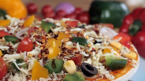 A delicious pizza loaded with cheese, corn, and olives kept on a turntable