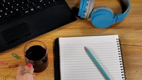 Woman's hand keeping a cup of black coffee on her work station - home office