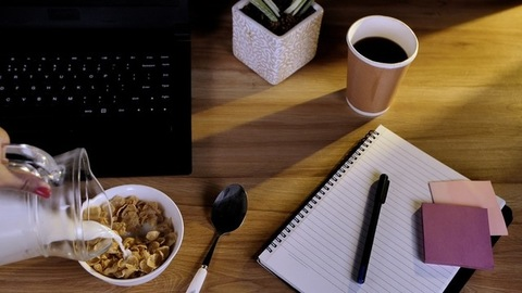 Fresh milk poured in a bowl of crunchy corn flakes kept on a wooden workplace