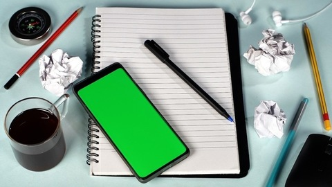 Pen dropping near a green screen chroma key device placed on a notepad - Work table