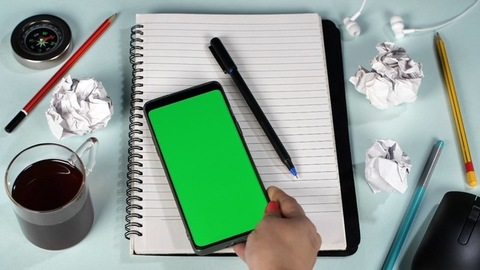 Female hands keeping a green screen chroma key device on a lined notebook - Home office work table
