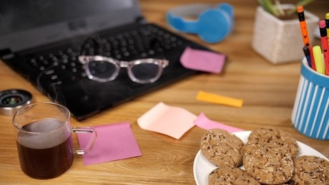 A pair of eyeglasses and sticky notes kept on the laptop on the office table - Work from home table