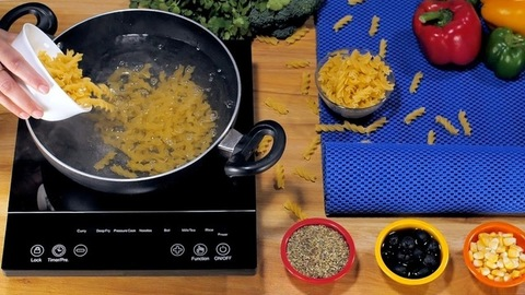 Fusilli pasta being dropped in hot water for boiling - popular Italian recipe