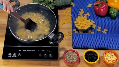 Woman's hand stirring farfalle pasta in a non-stick pot with a wooden spatula