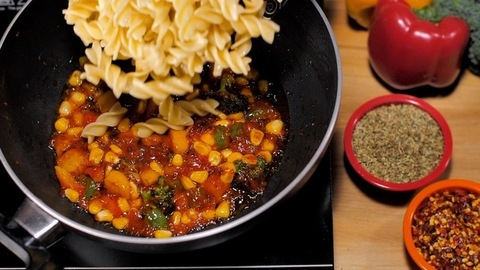 Steamed fusilli pasta added to stir-fried vegetables to prepare a tasty Italian dish