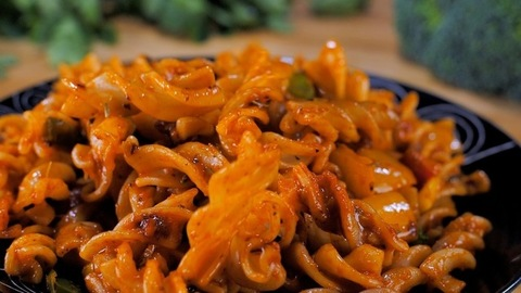 Red sauce flavored fusilli pasta falling on a plate - traditional Italian recipe
